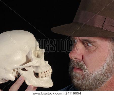 A Man In A Fedora Examines A Skull