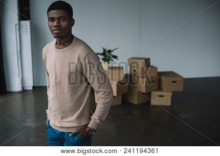 Young African American Man Standing With Hands In Pockets And Looking At Camera While Moving In New