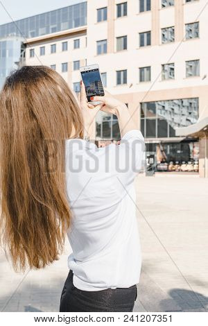 Girl In A Business Suit On The Streets Of The City With An Apple. A Woman Photographs On Her Mobile