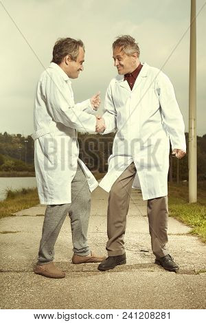 Two Older Retro Paramedic Freak Hunters In Medical Coats Celebrating Catching Crazy Man In Park