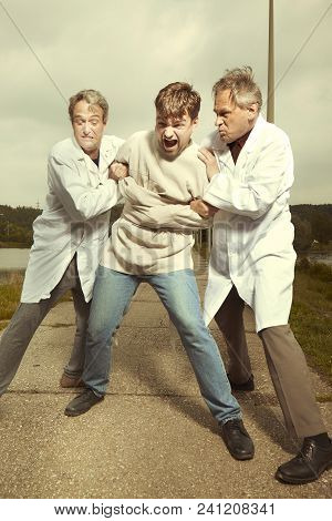 Two Older Retro Paramedic Freak Hunters In Medical Coats Catching Crazy Man To Straitjacket