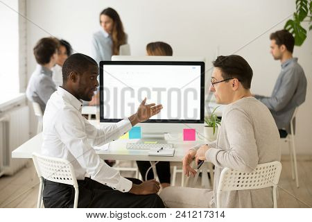 Serious Multiracial Colleagues Talking Discussing Project Together In Office, African Manager Explai