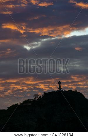 Jesus Figure From The Distance With Colorful Clouds In The Sunset. San Juan Del Sur, Nicaragua