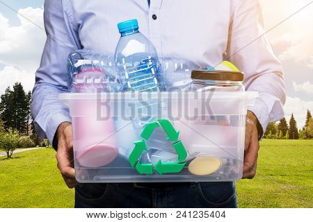 Person Carrying Container Full Of Used Plastic Bottles