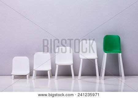 Empty Miniature Increasing Scale Of White And Green Chair On Grey Background