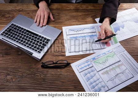 Businessperson Analyzing Graph With Laptop On Wooden Desk