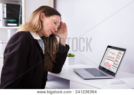 Side View Of A Tired Businesswoman With Graph On Laptop Screen