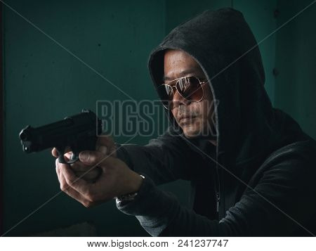 Hooded Man With A Gun In The Dark Room