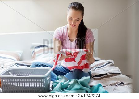 household and people concept - woman or housewife sorting laundry at home