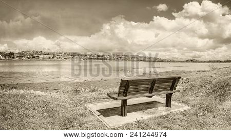 A lonely bench in a quay and river Lee on sunny cloudy day. Cork, Ireland Black white. poster