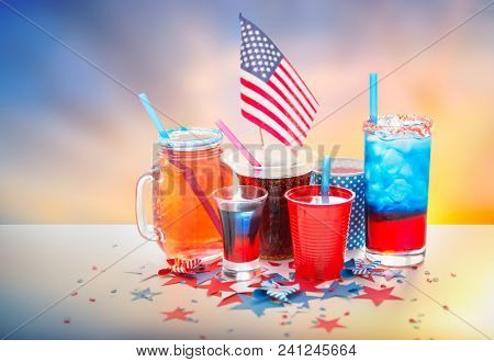 celebration, patriotism and holidays concept - close up of drinks in cups and glasses with american flag at independence day party over evening sky background