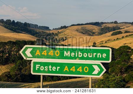 Signs On The South Gippsland Highway Pointing Towards Foster And Melbourne, Among The Rolling Hills