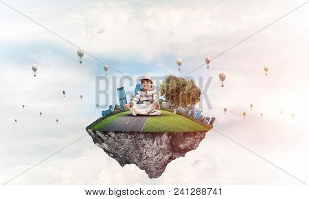 Young Little Boy Keeping Eyes Closed And Looking Concentrated While Meditating On Flying Island In T