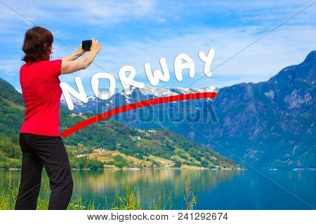 Tourism And Travel. Woman Tourist Taking Photo With Camera, Enjoying Mountains Lake Oppstrynsvatnet