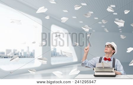 Young Man Writer In Hat And Eyeglasses Using Typing Machine And Pointing Upside While Sitting At The