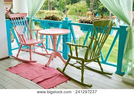 Pink And Green Wooden Rocking Chairs And Table On Porch Or Balcony. Two Relaxing Armchairs On Porch