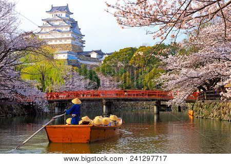 Group of Chinese tourists boating on the river near the Himeji castle at full cherry tree blossom, Unesco world heritage, Japan