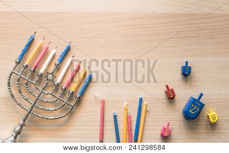 """Hanukkah/ Chanukah Jewish holiday background with menorah (Judaism candelabra) burned candles and Dreidel spin game toy with 4 Hebrew letters meaning """"A great miracle happened there"""" on white wood poster"""