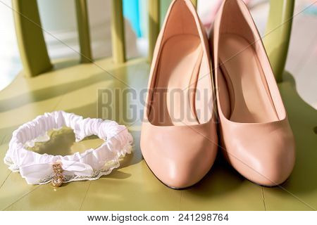 Beige Leather Bride's Shoes And Lace Garter On Chair, Copy Space. Wedding Accessories. Wedding Backg