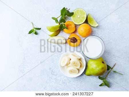 Fresh Ingredients for a Vegan Smoothie ( apricots, banana, pear, lime, mint and almnd milk)