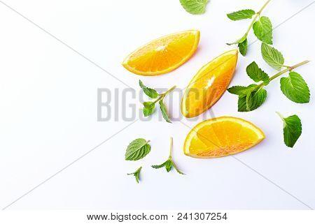 Fresh Orange and Mint Leaves on White Background; flatlay