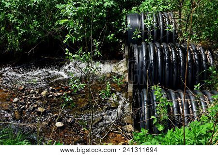 Three Black Plastic Drain Pipes Exit With Running Water In Brook Surrounded With  Stone, Uncut Grass