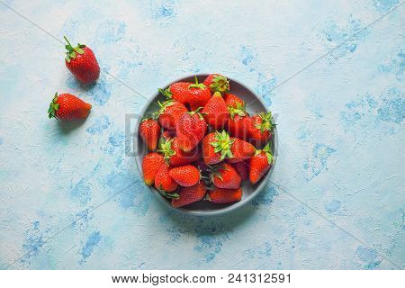 A Plate With Ripe Strawberries On A Blue Background.