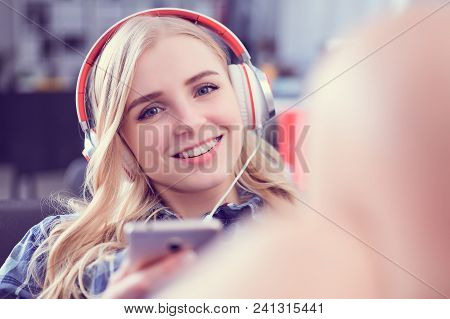 Happy Girl Listening Music And Selecting Songs On A Smart Phone Sitting In A Couch At Home.