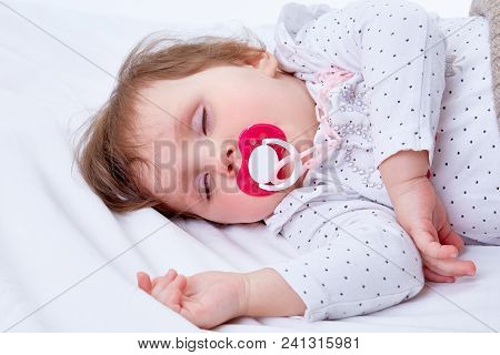 Portrait Of A Cute Toddler Girl With Big Red Dummy, Covered In Soft White Blanket Sleeping On White