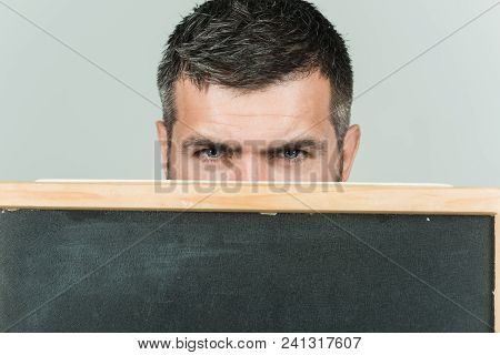Bearded Man Hiding Behind A Black Board. Cropped Photo Of Man's Head With Eyes Looking At Camera. Ma