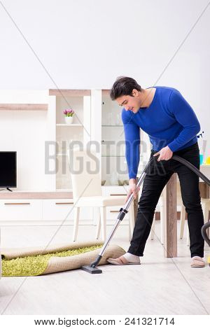 Young man vacuum cleaning his apartment