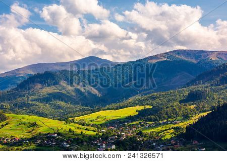 Beautiful Urban Landscape In Mountains. Village At The Foot Of The Mountain. Interesting Cloud Forma