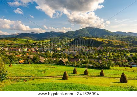 Beautiful Rural Landscape In Mountains. Haystacks On The Grassy Hills. Village At The Foot Of The Mo