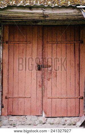 Old Wooden Door Closed On The Lock. Peeling Paint. House. Barn. Doors Red. The Door To The Hinges.