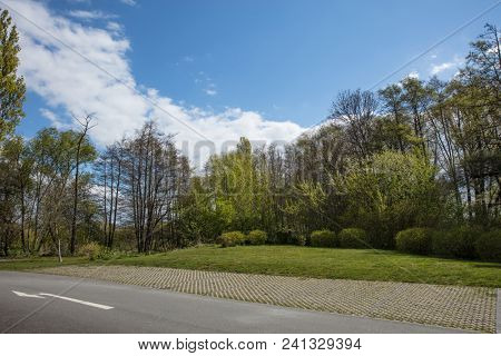 Parking strip as parking next to meadow and road with trees and sky