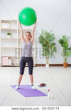 Young woman exercising with stability ball in gym