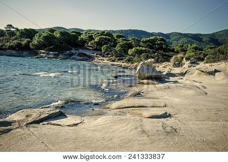 Nature Landscape On Sunny Summer Day. Nature Concept. Rocky Beach Washed By Waves, Sea And Green Tro