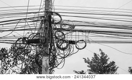 High Voltage Power Pole With Wires Tangled,wire And Cable Clutter. Potential Danger From A Mess Of W