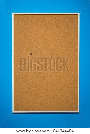 Cork Borad Or Notice Board With Wooden Frame Hanging On Blue Wall. Office Or Education Theme.