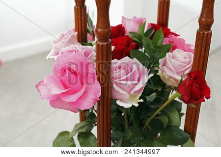 Beautiful Pink And Red Roses Flowers Bouquet In Between Four Wooden Columns Of A Side Table. Pink An