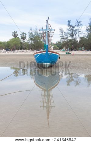 Wooden Fishing Boat On The  Low Tide Beach.
