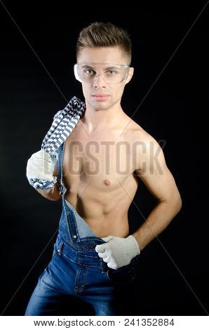 Sexy Guy In Overalls And Shirtless. Handsome Young Guy. Portrait. Handyman Shirtless. Smile And Joy.