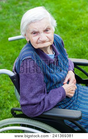 Old Lady Sitting In Wheelchair Suffering From Dementia Spending Time Outdoor
