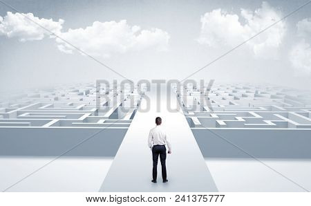 Businessman going straight ahead on a wide road between mazes