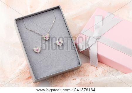 Jewelry Set Of Heart Necklace And Stud Earrings With White And Pink Crystals In Gift Box On Lace Bac
