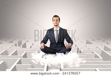 Young businessman meditate in yoga position on a cloud with infinity maze concept