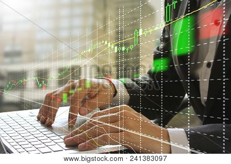 Double Exposure Of Businessman Using The Laptop With Stock Market Or Financial Graph For Financial I