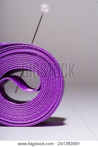 Hank silk purple ribbon with a pin, close-up, macro on a grey background poster