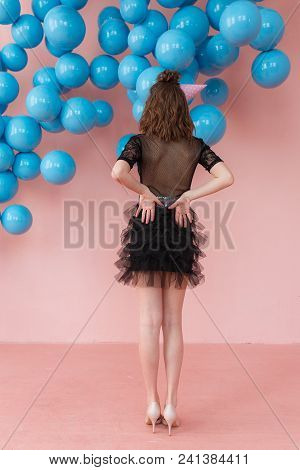 Back View Of Young Woman In Black Dress Posing On Pink Wall Background, Looking To Blue Balloons.