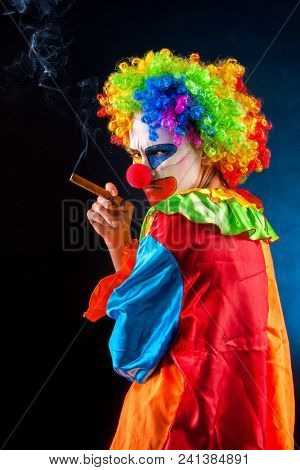 Mad clown on black background. Woman smoking cigar. Portrait of crazy female. Scary clowns falling victim to vigilante violence as terrified residents. People who hate their work. Suit for Halloween.